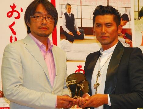 本木雅弘と一緒にグランプリ受賞を喜ぶ脚本の小山薫堂(左)