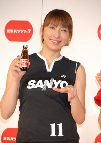 笑顔でオロナミンCを手に持って紹介する小椋久美子
