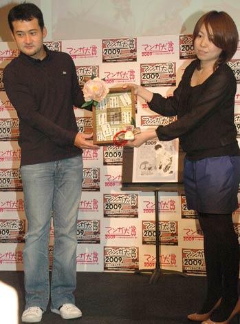 プレゼンターとして登場した、前年大賞作の原作者・石塚真一氏(左)と、代理で盾を受け取る『ちはやふる』の担当編集者