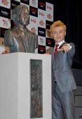 自身の銅像を横にポーズを決めるつるの 【「東京ドームシティ市長就任会見」にて】
