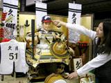 イチロー選手をモデルにしたオリジナルの五月人形(子供大将)「親のねがい大将」に帽子を被せる様子