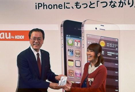 KDDIデザイニングスタジオ(東京・原宿)で行われた『iPhone 4S』発売記念セレモニーに登場した田中孝司社長(左)と1番目に同製品を手にした女性 (C)ORICON DD inc.