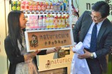 女性向け自販機『naturacure(ナチュラキュア)』お披露目イベントの模様。デザインを担当した彫刻家・はしもとみおさん(左)から、JR東日本ウォータービジネス・鈴木浩之社長へ、ロゴの原型になった木彫のブランドネームがサプライズで贈られた (C)oricon ME inc.