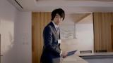 夕暮れのオフィスでコチラを見つめるスーツ姿の斎藤工
