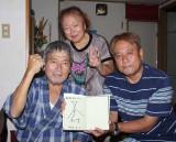 息子が芥川賞を受賞したことに「たいしたもんや」と喜ぶ父の己敏さん(左)=16日、名護市汀間