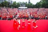 雨にもかかわらず赤いものを身につけた2600人のファンが集結