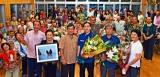 花束を手にする又吉直樹さん(中央)と両親(右)、ピースサインで受賞を祝う区民ら=12日、名護市汀間区公民館