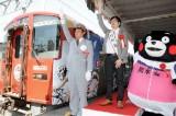 長沼範裕監督(中央)らの合図で出発するラッピング列車=23日、JR熊本駅