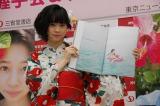 1st写真集『ひより日和。』の中からお気に入りのページを開いて見せる桜田ひより