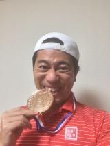 銅メダルを噛む仕草