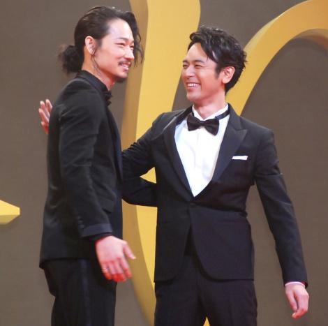 抱擁しあう(左から)綾野剛、妻夫木聡=映画『