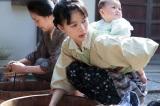NHK連続テレビ小説『べっぴんさん』第12回。疎開先の近江で、さくらをあやしながら、洗濯しているすみれ(C)NHK