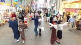 広島・本通商店街でダンスを踊るメガネをかけた通行人 『イロドリ Journey』の場面カット