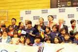 国分も子供たちとにこやかに参加、小旗を振りながらの記念撮影
