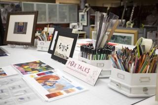 デザインチームの作業台には展示用のイラストとカラフルなペンがならぶ