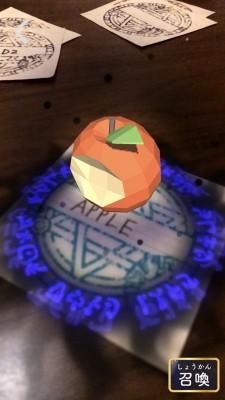 ペンで「APPLE」と書いた魔法陣カードをアプリ『SPELL MASTER』で見るとリンゴの3Dモデルが召喚される