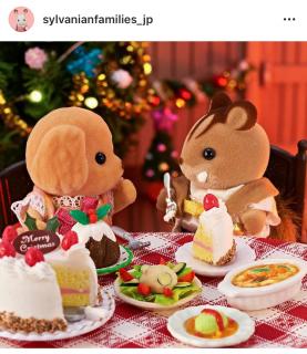 クリスマスケーキを食べるトイプードルの男の子とくるみリスの男の子