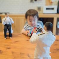 トーマスのおもちゃで遊ぶたろさんをカメラで撮るミフネさん