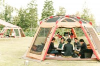 スーツ姿の男性たちがテント内で会議を開く異様な光景
