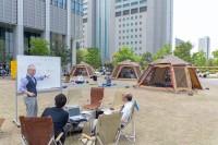 すぐそばにビルがありながらもテント内で開かれているビジネス会議