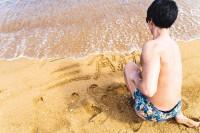 砂浜に好きな筋肉の部位を書くマッチョ