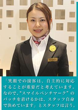 """「笑顔での接客は、自主的に対応することが重要だと考えています。なので、""""スマイルベンチマーク""""のバッチを着けるかは、スタッフ自身で決めています」います。」とスタッフは言う"""