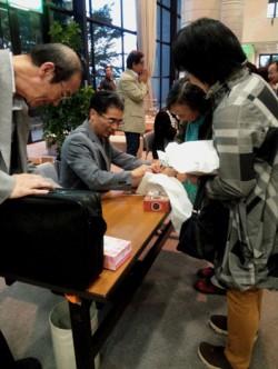 サインに応じる富澤氏。地元ではタクシーの運転手でも知っている