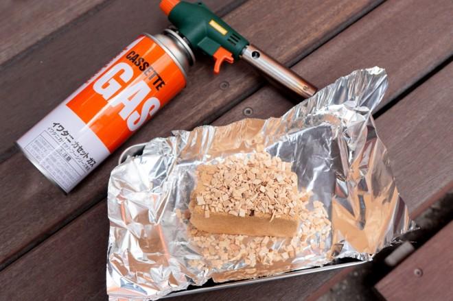 3.ステンレスのバット(またはボウル)にアルミホイルを敷き、スモークウッドを載せる。ライターなどではなかなか火が付かないので、バーナーで点火する。火の回りを良くするために、最初はウッドの火がついた部分にチップを載せる。4.スモーカーの下部に点火したスモークウッドを入れる。 ※段ボールスモーカーで燻煙をする場合は、燃え移らないように、細心の注意を払うこと。