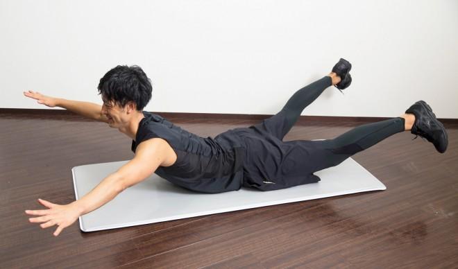 【2】へその下くらいが床に接し、腹をへこませるイメージで、ゆっくりと背中を反るようにして手足を伸ばす感じで上げていく。反り過ぎには注意。反動をつけるのも避ける。 ゆっくり【1】に戻る。動作中は呼吸を止めないで、自然に続ける。