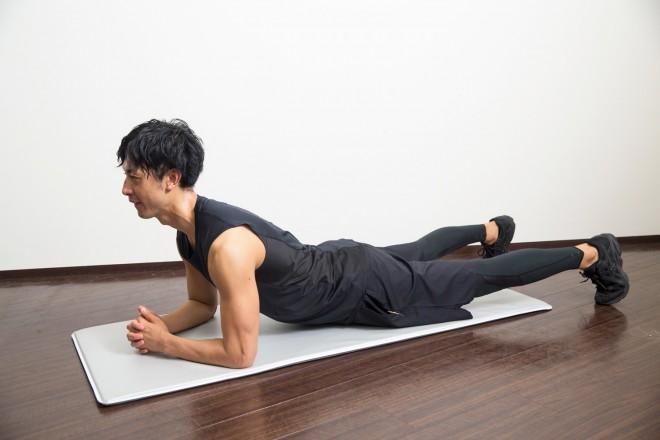 【1】うつぶせになり、つま先を立てる。両手を前で組み、両肘は90度の角度で、上半身を起こす。