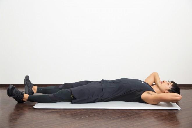 【1】あおむけになり、両手を頭の後ろで組んで真横に広げ、脚を伸ばす。