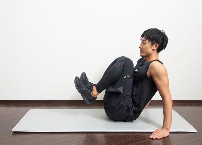 【2】踵(かかと)を床から浮かせ、息を吐きながら膝を軽く曲げて胸に近づけるように引きつける。反動をつけず、ゆっくりと行う。意織はおなかの下の部分に。