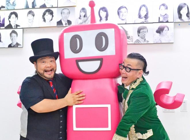 「これからも頑張って!」とPASMOのロボットに抱きつきながらエールを贈る髭男爵