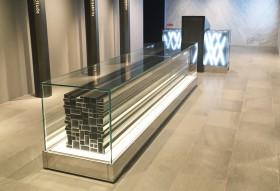 普段見えない建築資材を使ったオブジェは「固い気持ち」「結束」と透明ケースの中で見せる事で透明性と、縁の下の力持ちの職人に光を照らしていく事を表現。