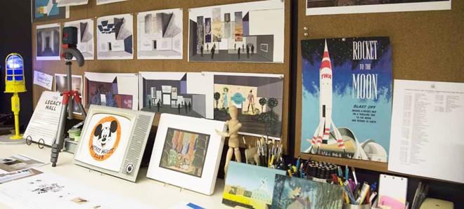 展示会イベントのポスターやレイアウトが掲示されているデザインチームのオフィス