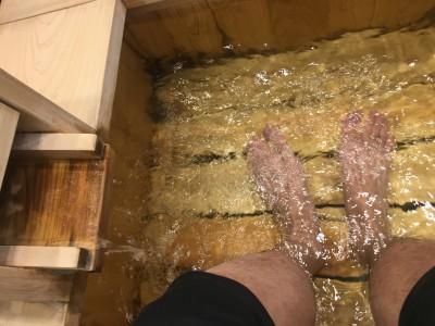 仕事の合間に足湯に浸かる松阪 温泉ソムリエをもつほど造詣も深い