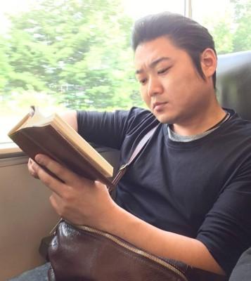 移動中は好きな本を読んでリラックス 絵になる男です!