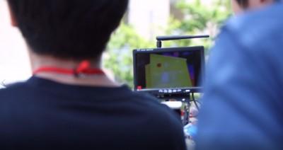 ドローンが撮影した赤外線カメラの情報を、現場で確認するスタッフ。