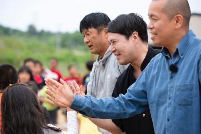 現地のこどもとハイタッチ。チビっ子との交流に自然と頬がゆるむタカトシと武田修宏(C)UHB/YOSHIMOTO KOGYO