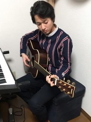趣味ギターを弾く青山新