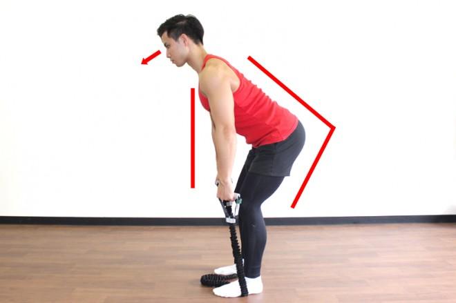チューブを使ったベントオーバーロウ [1]足でチューブを踏みながら足を肩幅に開いて立ち、つま先は少しだけ外に開く。お尻の筋肉に張りを感じた状態で45〜60°に前傾する。両手にチューブを短く持ち、手が肩の真下にくるように腕をまっすぐに伸ばす。