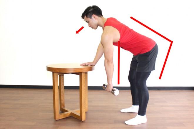 ワンハンドで行うベントオーバーロウ [1]椅子やベンチなどに片手を置き、脚を肩幅に、つま先は軽く外に開いて立つ。お尻の筋肉に張りを感じた状態で45〜60°に前傾する。ダンベルを持ち、手が肩の真下にくるように腕をまっすぐに伸ばす。