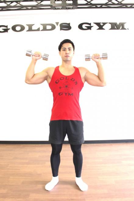 ショルダープレス(ダンベル) [1]脚を肩幅に開いて真っ直ぐに立つ。床と平行になるよう両手にダンベルを持ち、腕を90°に曲げる。