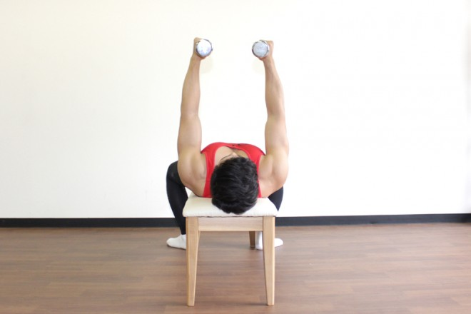 ダンベルフライ [1]ベンチに仰向けになり、両手にダンベルを持つ。腕を真っ直ぐに伸ばしながら、肩の真上にダンベルを持ち上げる。胸を張り、手のひらが向かい合うパラレルグリップで構える。