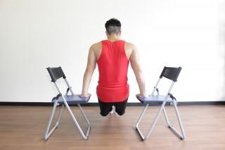 後ろからの写真 1.体の両側に椅子を置いて手のひらをつき、腕を真っ直ぐ伸ばして胸を張る。足は揃えて自然に真っ直ぐ伸ばし、踵を床につける。