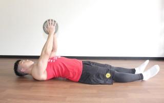 横からの写真 2.真っ直ぐ肘を伸ばしてプレートを高く上げる。上にプレートを押しきったときに、大胸筋の収縮を意識する。1〜2の動きをゆっくりと繰り返す。