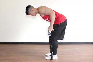 横からのアングル 1. 足を腰幅に開き、上体を深く倒す(床から45度程度の角度)。足で押さえてチューブの長さを調節し、X字になるように両手でチューブの端を持つ。