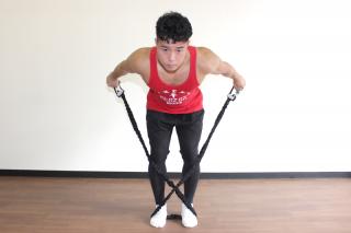 正面からのアングル 2.肘を真っ直ぐに伸ばしてチューブを後ろに引き伸ばす。1〜2を繰り返す。