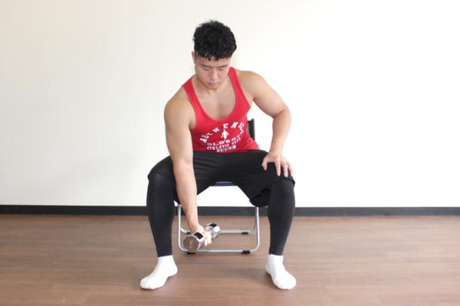 1. 足を肩幅よりやや大きく開いてベンチや椅子に座る。片手でダンベルを持ち、二の腕を腿に当てて肩と肘を固定する。