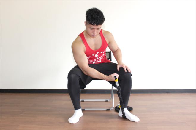 1. 足を肩幅よりやや大きく開いてベンチや椅子に座り、片足でチューブを押さえて固定する。足と反対の手でチューブの端を持ち、二の腕を腿に当てて肩と肘を固定する。